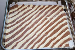 Using two piping bags, pour batter into the baking pan in long alternating rows as seen in the picture.