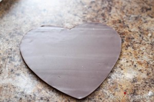 Trace the outline of your heart pan onto a piece of paper. Sprinkle some powdered sugar onto your work surface and roll out fondant with a rolling pin. Cut out the heart shape.